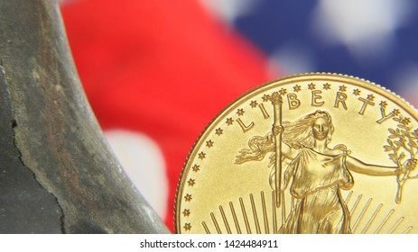 "Tight Focus Highlighting Torch In ""Liberty"" Of US One Ounce Gold Eagle Balanced Upright Along Side Cracked Bell In Front Of The Colors Of Old Glory"