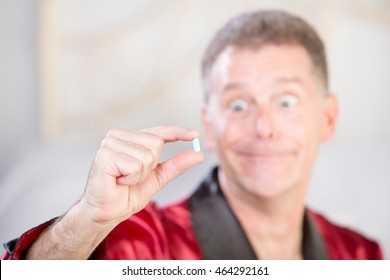 Tight focus on blue pill to combat erectile dysfunction with silly man in background