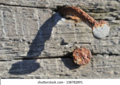Tight focus on the head of a rusty nail in an old piece of wood