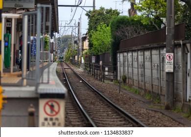 Tight railroad tracks and platform for local train transportation in Kamakura, Japan