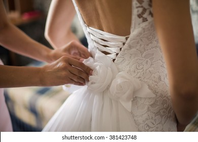 tighten wedding dress on bride