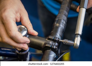 Tightening of a bicycle handlebar stem with the use of a small torque wrench. Proper way to tighten a bicycle handlebars. Bicycle service in a worshop.