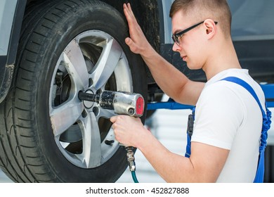 Tightening bolts. Portrait of a young mechanic tightening bolts on wheels with a pneumatic wrench