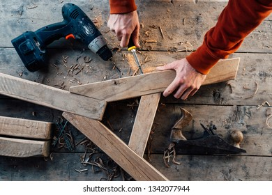 tightening the screw with a screwdriver in a wooden block, making furniture