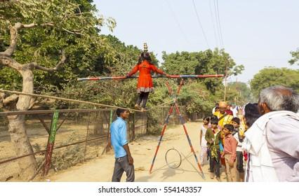tightrope walker girl on the street. crowd pilgrims go on Govardhan Parikrama Marg. India Govardhan, November 2016
