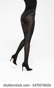 Tights. Black covering tights. Female legs in shoes on a stiletto dressed in tights Female legs in black tights on a white background.