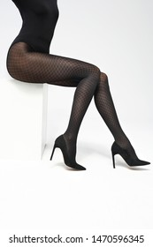 Tights. Female legs in black tights on a white background.