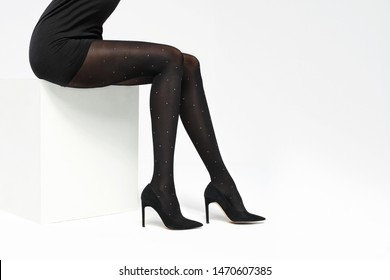 Tights. Woman's legs in black tights on a white background.