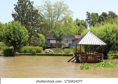 Tigre delta in Argentina, river system of the Parana Delta North from capital Buenos Aires. Lush vegetation, traditional wood house by wooden pier and orange water that carry clay to Rio de la Plata.