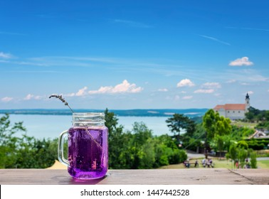 Tihany abbey with the lake Balaton blurred in the background and a lavender beverage focused in the front