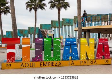 TIJUANA, BAJA CALIFORNIA, MEXICO - OCTOBER 22, 2018:  A giant colorful sign at Playas de Tijuana with the International Border wall between Tijuana and San Diego, California in the background.
