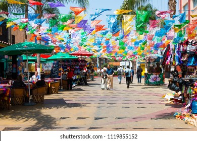 TIJUANA, BAJA CALIFORNIA/MEXICO - JUNE 20, 2018:  People shop and dine at Plaza Santa Cecilia, a historic Mexican square with colorful hanging flags.