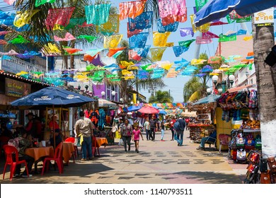 TIJUANA, BAJA CALIFORNIA/MEXICO - JUNE 20, 2018:  People shop and walk below colorful hanging flags at Plaza Santa Cecilia, a historic Mexican square in the heart of the city.