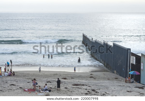 TIJUANA, MEXICO - JULY 26, 2014: Beach goers enjoy a day at the beach along the border fence in Tijuana, Mexico on a summer day