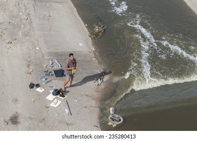 TIJUANA, MEXICO - NOVEMBER 13, 2014: A homeless man dries his clothes as he stands in his boxers and with a bandaged ankle along the heavily contaminated Tijuana River