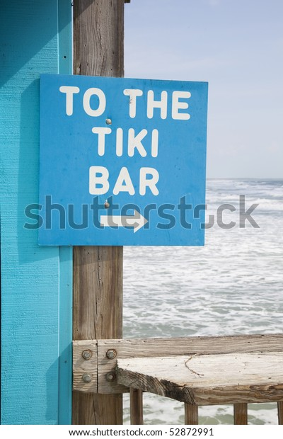 To the tiki bar sign with breaking waves in background.