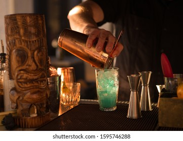 A tiki cocktail is mixed on a bartop.