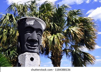 A tiki pole with palm trees and blue sky.
