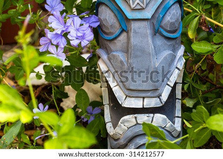 A Tiki Statue En Garden/ Tiki Garden Flower/ A Tiki Head Surrounded By  Plumbago