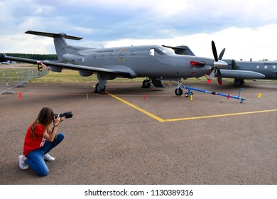 TIKKAKOSKI, FINLAND - JUN 16, 2018 : Woman taking picture of 'Finnish Air Force Pilatus PC-12/47' at Finnish Air Force 100th Anniversary Airshow