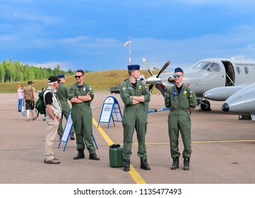 TIKKAKOSKI, FINLAND - JUN 16, 2018 : Group of pilot standing and talking in front of military airplane at Finnish Air Force 100th Anniversary Airshow