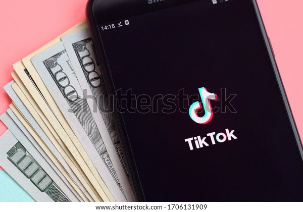 Tiktok application on samsung smartphone screen and dollar bills. TikTok is a popular video-sharing social networking service owned by ByteDance