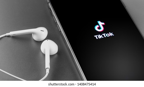 TikTok logo on the screen iPhone with Earpods. TikTok is app to create and share videos. Moscow, Russia - May 22, 2019