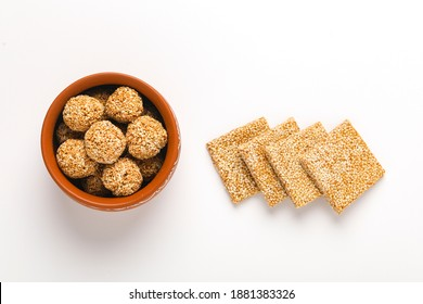 Til chikki and sesame seed ball on white background is an Indian sweet dish made with jaggery and sesame seeds.
