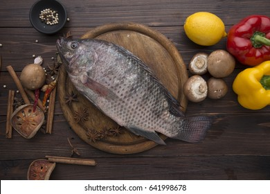 Tilapia fish and garnish and bell pepper on wooden table