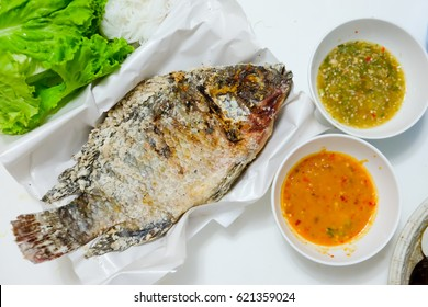 Tilapia fish grilled with Salt  and have Spicy Sauce, Thai foods style placed