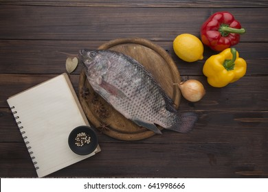 Tilapia fish and notepad and bell pepper on wooden table