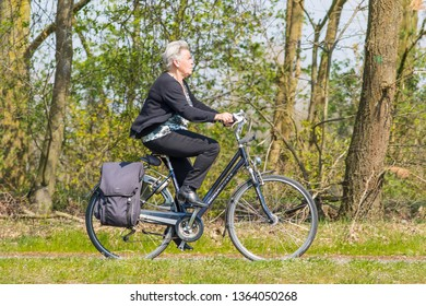 TILBURG-APRIL 7, 2019. Cycling elderly woman enjoys the spring weather. According The European Cyclists Federation, Holland is the European bike safety top. Most of the Dutch don't even wear helmets.
