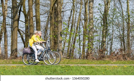 TILBURG-APRIL 7, 2019. Cycling elderly women enjoys spring weather. Holland has a population of 17 million people and 22 million bikes. The country has over 35,000 kilometers of dedicated bike paths.