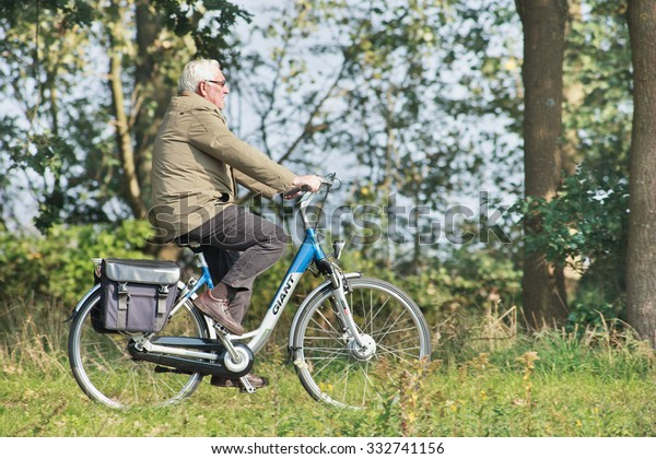 TILBURG-HOLLAND-OCT. 4, 2015. Senior on a Giant e-bike. Giant is a Taiwanese company, recognized as the world's largest bicycle manufacturer with production facilities in Taiwan, Holland and China.