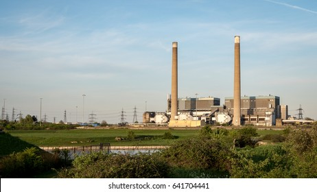 Tilbury Power Stations. The decommissioned coal powered Tilbury power stations on the River Thames with pylons in the background feeding energy into the UK National Grid electricity network.