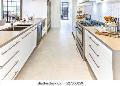 Tile floor with a hallway through the kitchen with ovens, stoves, taps with sink fixed to the counter, there are utensils on the cupboards