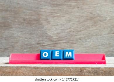 Tile letter on red rack in word OEM (Abbbreviation of Original Equipment Manufacturer) on wood background