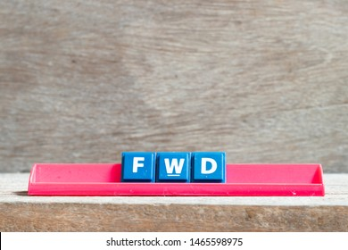 Tile letter on red rack in word FWD (Abbreviation of forward) on wood background