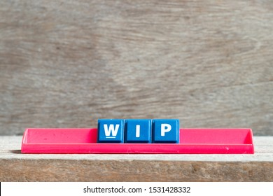 Tile letter on red rack in word WIP (Abbreviation of work in progress) on wood background