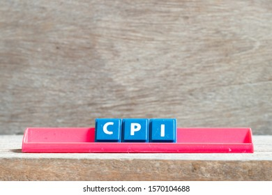 Tile letter on red rack in word CPI (abbreviation of Consumer Price Index) on wood background