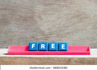 Tile letter on red rack in word free on wood background