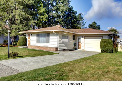 Tile roof siding house with a garage and concrete drive way