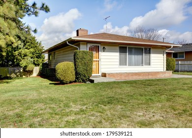 Tile roof siding house with a green lawn