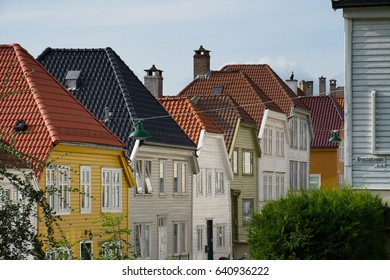 Tile roofs of Bergen, Norway and green street lamps in a summer day with blue sky
