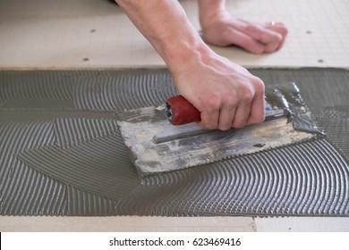 Tile setter laying down thinset for a tiling project during a major house renovation.