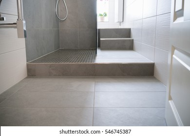 Tiled floor and step into a glass fronted modern shower cubicle in a neutral toned monochrome bathroom