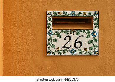 tiled letterbox for home against orange wall