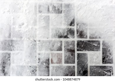 Tiled pavement covered with snow. Footprints on slippery surface. Abstract winter texture. Copyspace for text
