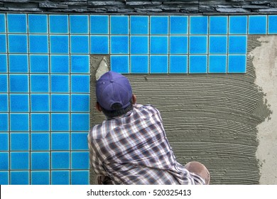 Tiled pool. The man hand while using spacer for installing tiles. construction work.Construction Pool.Technicians are tiled swimming pool.