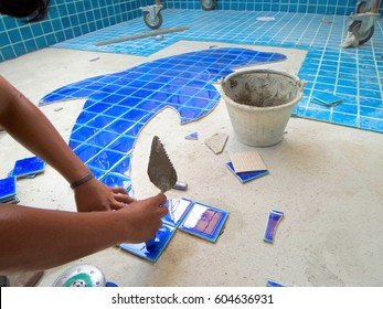 Tiled pool. The man hand while using spacer for installing tiles.